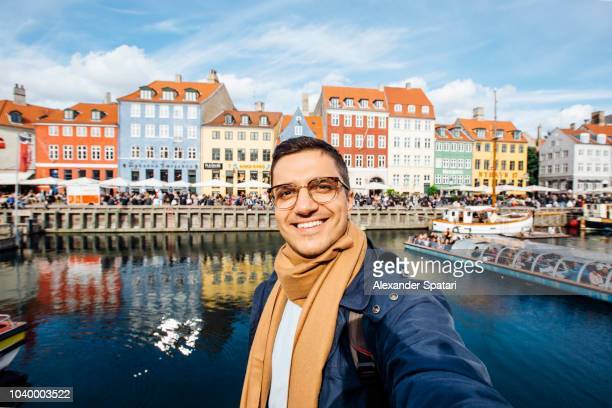 young man in eyeglasses taking selfie at nyhavn harbor in copenhagen, denmark - self portrait photography stock pictures, royalty-free photos & images