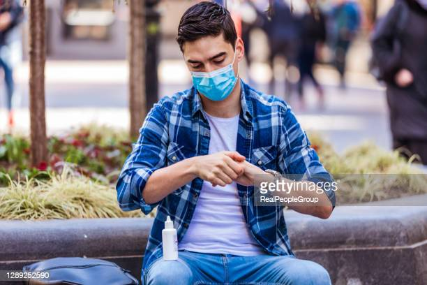 jonge mens in gezichtsmasker die zijn hand met antiseptic reinigt - real people stockfoto's en -beelden
