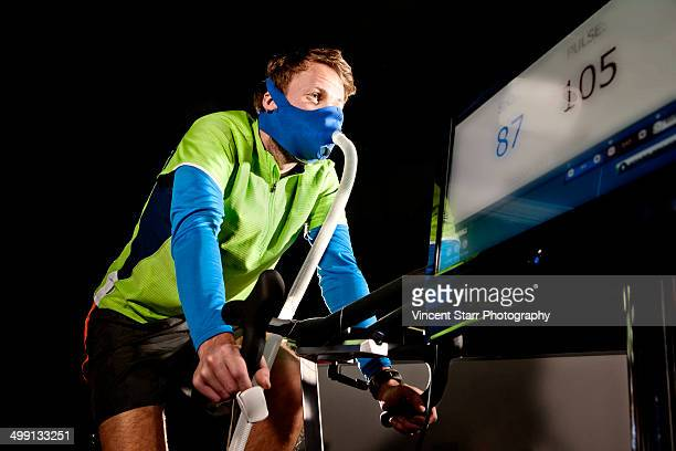 Young man in face mask on gym exercise cycle in altitude centre