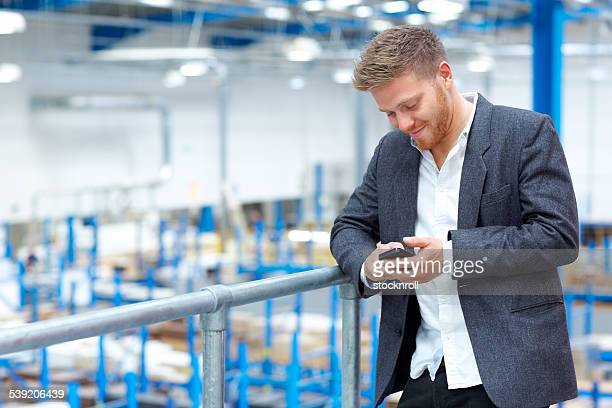 Young man in factory using mobile phone