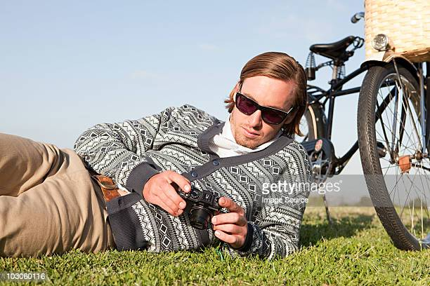 Young man in field with camera and bicycle