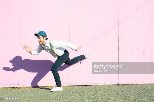 young man in front of pink construction barrier, balancing on one leg - standing on one leg stock pictures, royalty-free photos & images