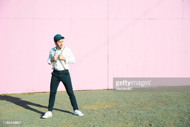 young man in front of pink construction barrier, holding onto his suspenders - construction barrier stock pictures, royalty-free photos & images