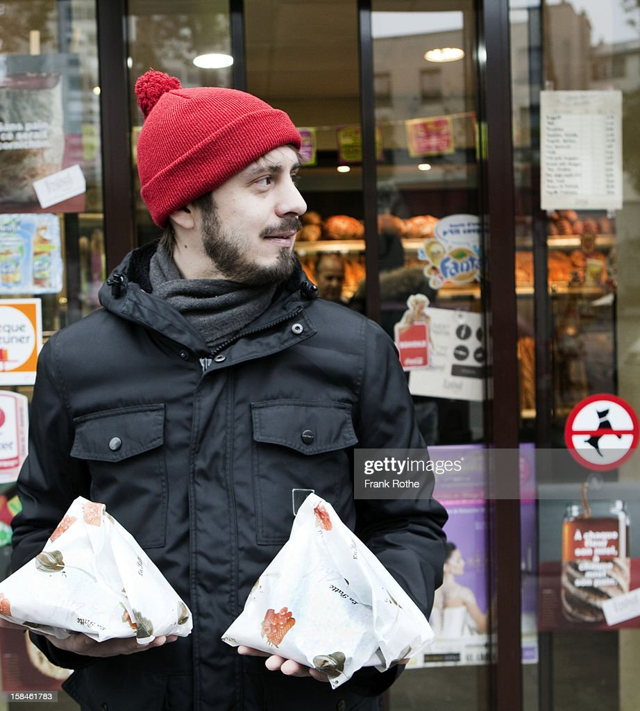 young man in front of store holding two packages : Foto de stock