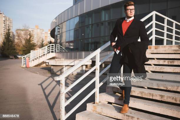 young man in front of the office building on a sunny day - businesswear stock pictures, royalty-free photos & images