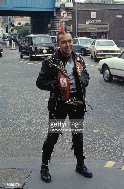 A young man in full punk outfit of boots bondage trousers studded leather belts and jacket and mohican hairstyle circa 1980