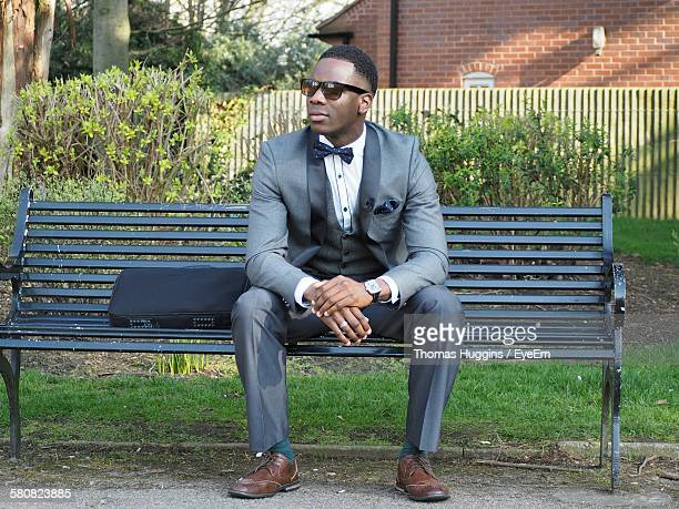 Young Man In Full Suit Sitting On Park Bench