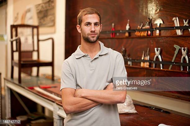 young man in furniture workshop - polo shirt stock pictures, royalty-free photos & images