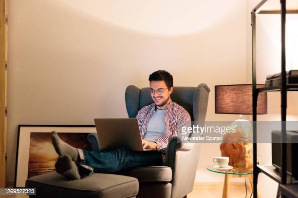 young man in glasses working at laptop at his apartment in the living room at night - males stock pictures, royalty-free photos & images
