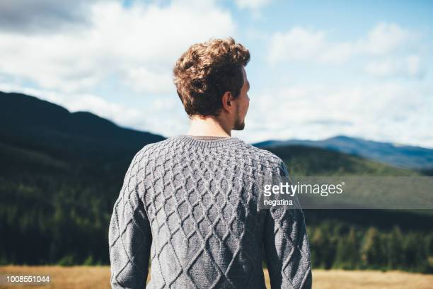 young man in gray sweater stands back to camera looking on the mountains - sweater stock photos and pictures