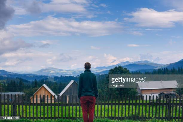 young man in green sweater and red pants standing back to the camera in front of beautiful mountain landscape