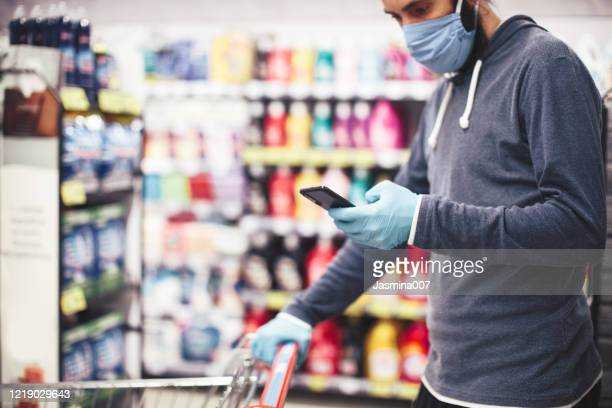 young man in grocery shopping - glove stock pictures, royalty-free photos & images