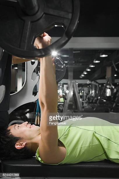 Young man in gym lifting weight, side view