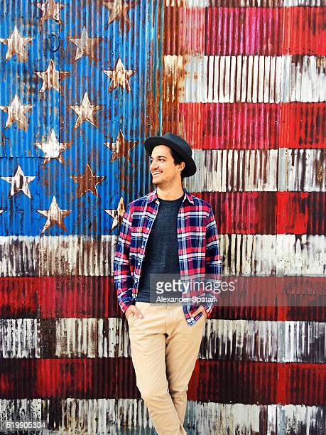 Young man in hat laughing against American flag background