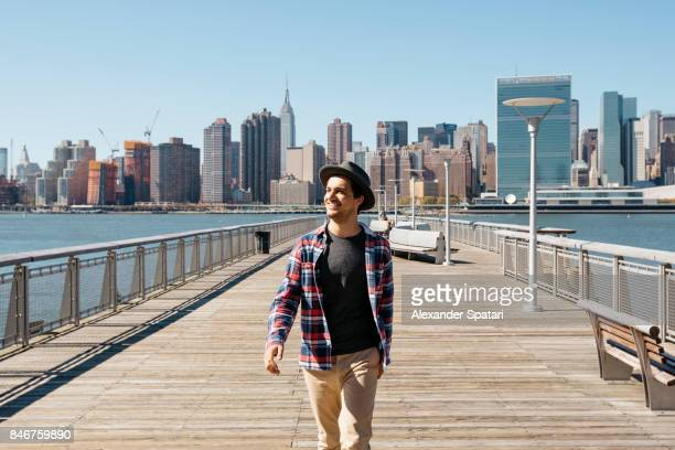 Young man in hat walking and laughing against New York City skyline