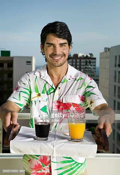 Young man in hawaiian shirt, holding tray with drinks, portrait