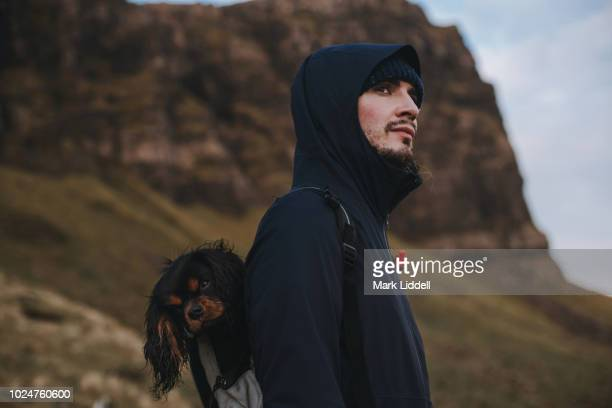 Young man in hiking gear carrying a Cavalier King Charles Spaniel in his backpack