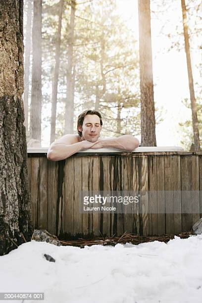 young man in hot tub in forest, snow in foreground, sunset - halbbekleidet stock-fotos und bilder