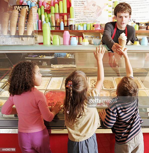 Young man in ice cream shop serving ice cream to children (4-6)