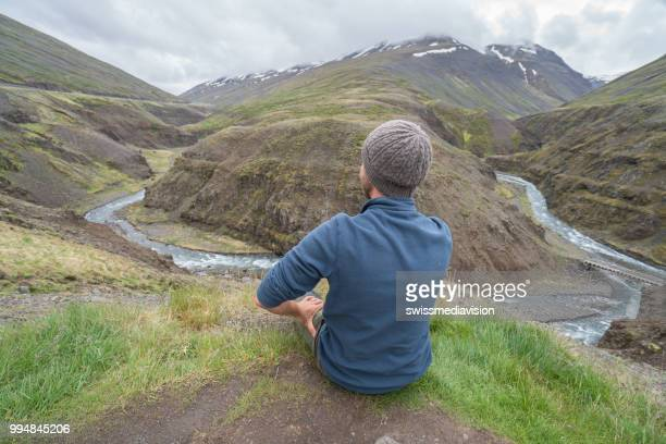 Young man in Iceland contemplating canyon from top of it