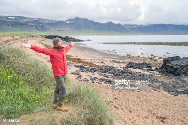 Young man in Iceland stands on top of a beach arms outstretched for freedom