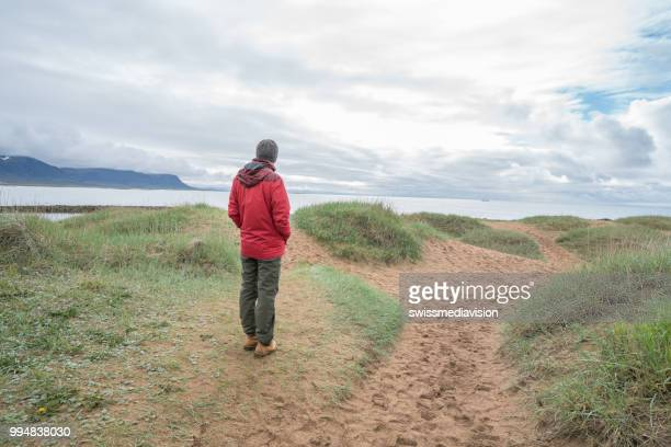 Young man in Iceland stands on top of a beach contemplating the landscape