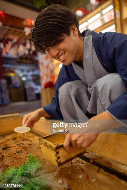 young man in kimono scooping goldfish in matsuri - three quarter length stock pictures, royalty-free photos & images