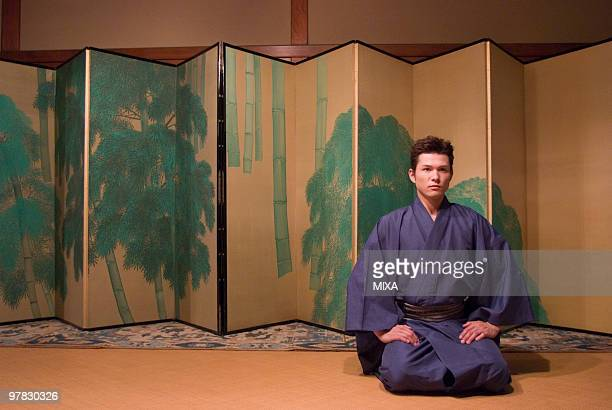 Young man in kimono sitting in front of folding screen