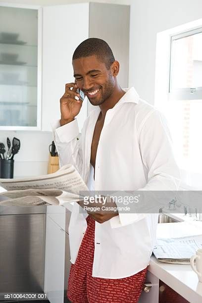Young man in kitchen, reading newspaper and talking on cell phone