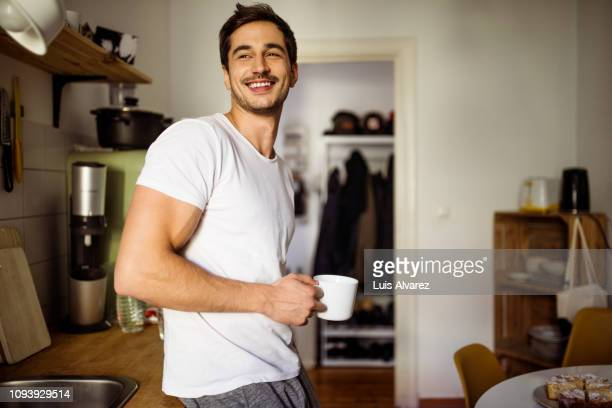 young man in kitchen with coffee - kaffee getränk stock-fotos und bilder