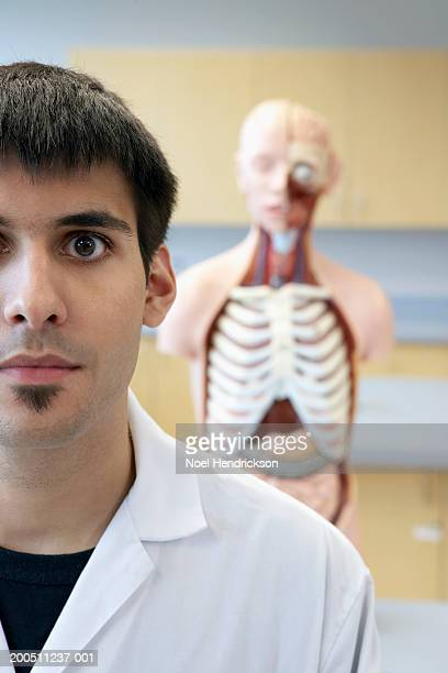 Young man in laboratory, anatomical model in background