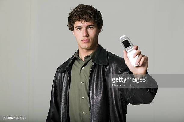 Young man in leather jacket holding mobile phone