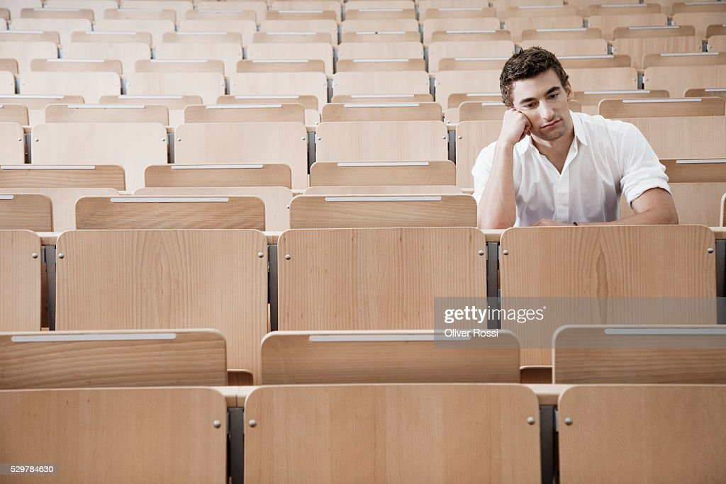 Young man in lecture hall : Stock Photo