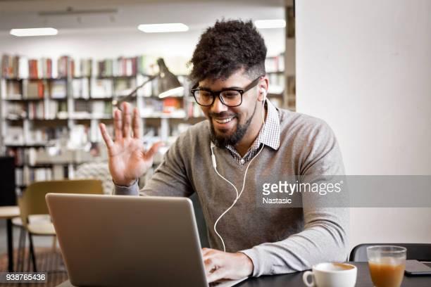 Junger Mann in der Bibliothek auf Laptop Kaffee trinken