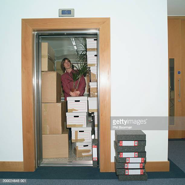 Young man in lift holding potted plant, surrounded by packing boxes
