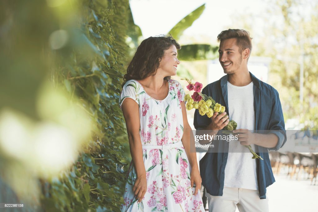 Young man in love giving flowers to his girlfriend : Stock Photo