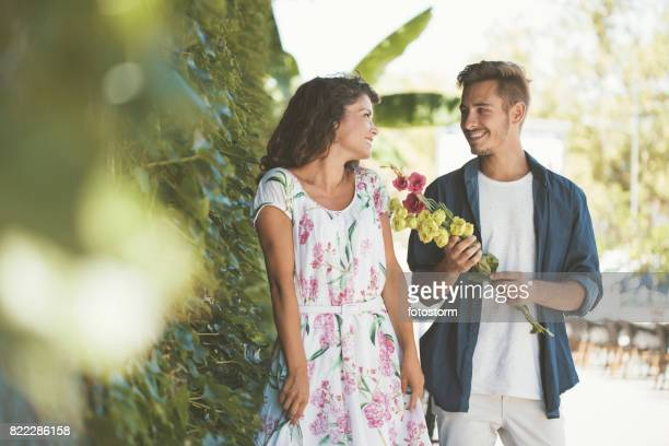 Young man in love giving flowers to his girlfriend
