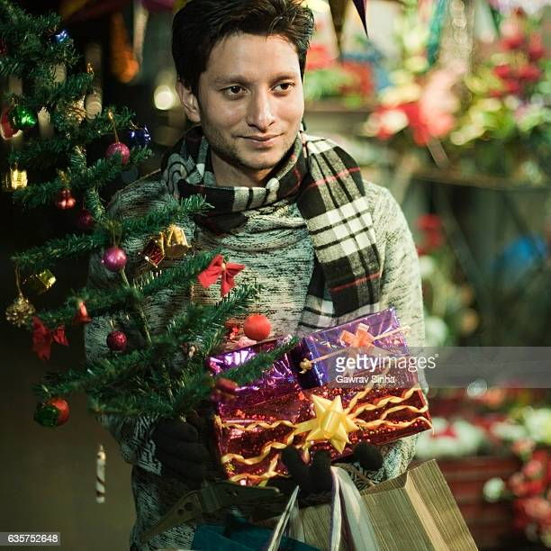 Young man in market shopping for Christmas and new year.