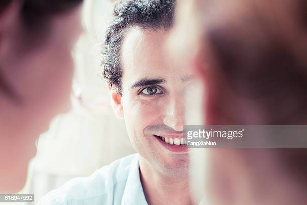 Young man in meeting smiling