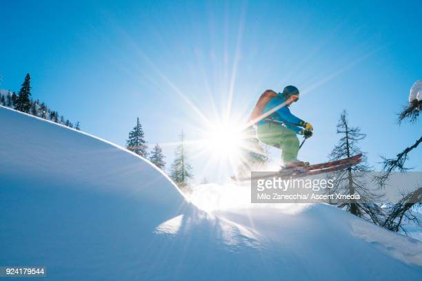 Young man in mid air jump above forest after fresh snow