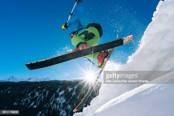 Young man in mid air jump above Swiss valley after fresh snow