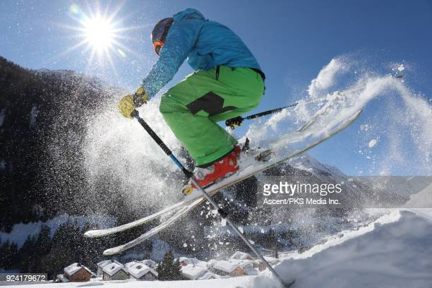 young man in mid air jump above swiss village after fresh snow - ski pole stock pictures, royalty-free photos & images