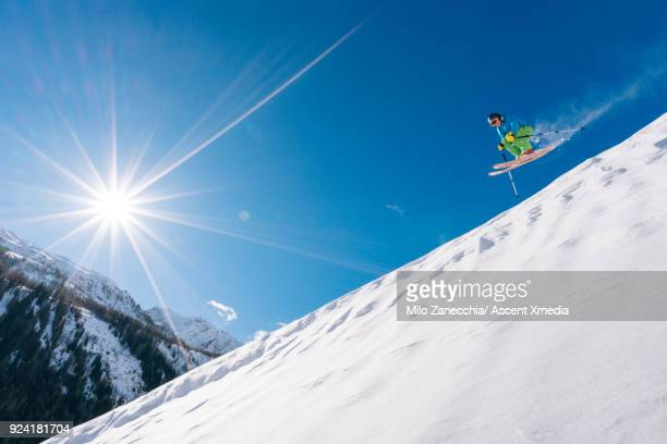 Young man in mid air jump above Swiss village after fresh snow