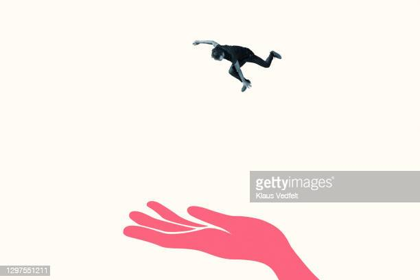 young man in mid-air falling on red hand - trust stock pictures, royalty-free photos & images
