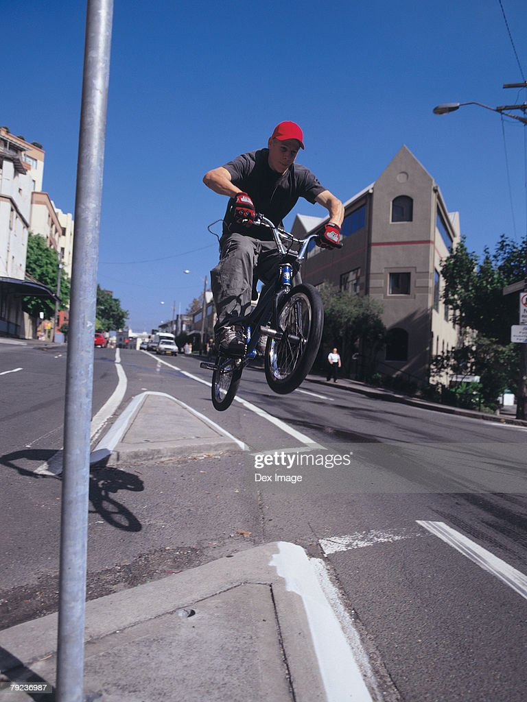 Young man in mid-air jump on bike, city scene : Stock Photo