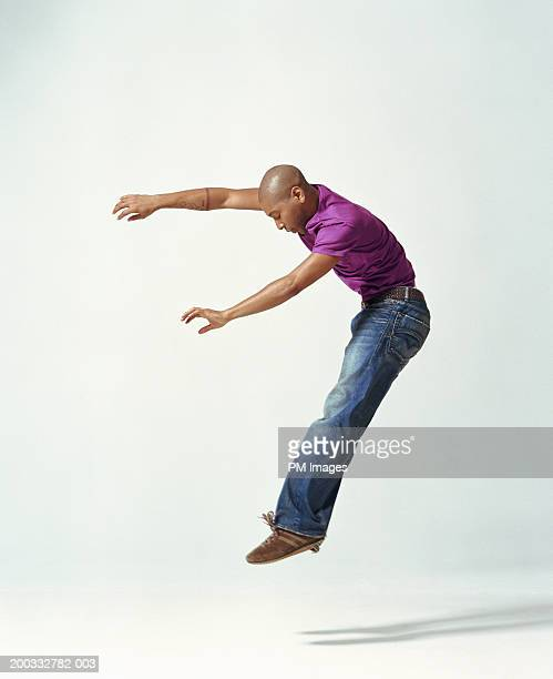 Young man in midair with arms out, side view