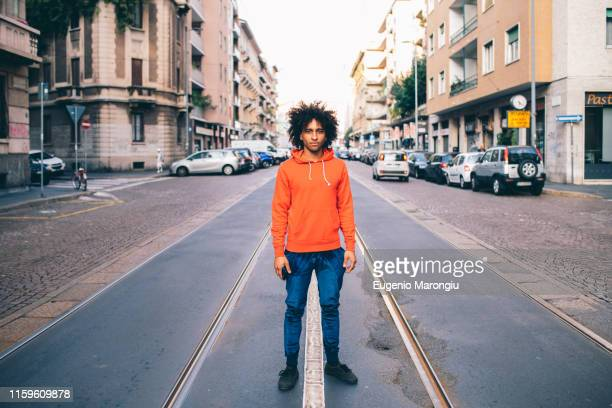 young man in middle of city street, milano, lombardia, italy - パーカー服 ストックフォトと画像