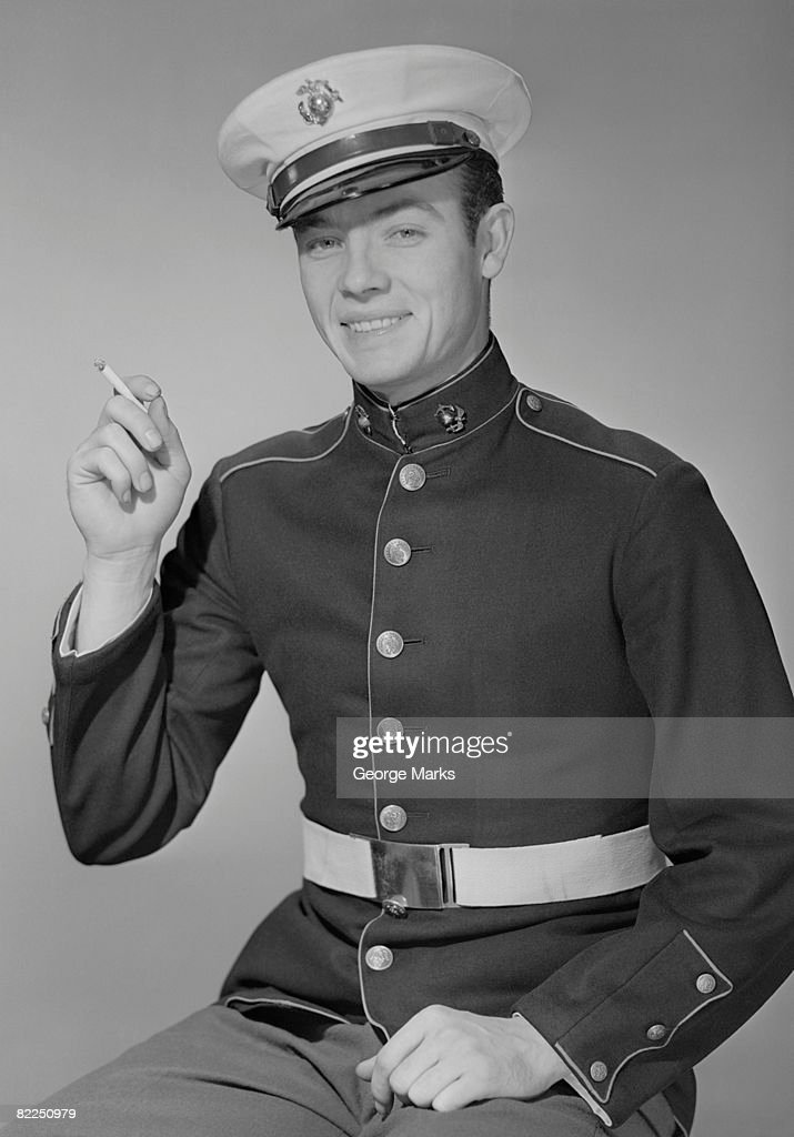 Young man in military uniform with cigarette, portrait : Stock Photo