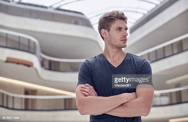 young man in modern office building - sideways glance stock pictures, royalty-free photos & images