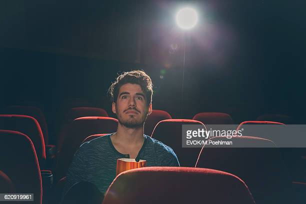 Young man in movies theater watching a movie
